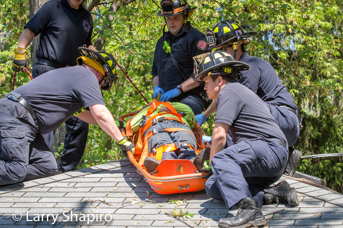 Buffalo Grove firemen rescue a tree worker that fell 30 feet onto a garage roof at 271 Lincoln Terrace 5-21-15 Larry Shapiro photographer shapirophotography.net
